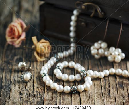 Pearl necklaces and earrings on wooden table. Vintage concept