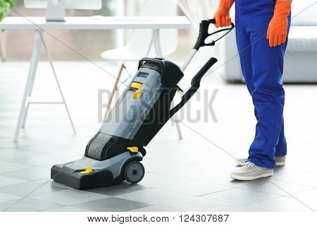 Young janitor with washing machine cleaning floor in office