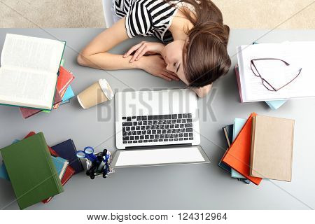 Young woman fell asleep while using laptop at the table