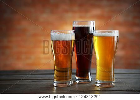 Glasses with different sorts of craft beer on brick wall background