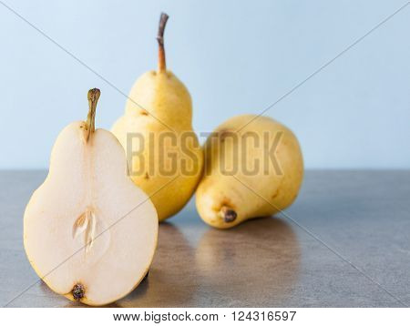 Whole and halved yellow Corella pears with copy space poster