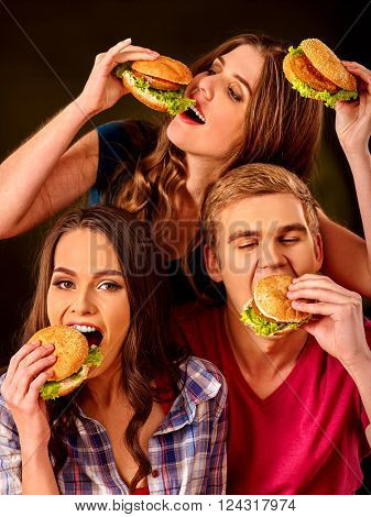 Group people eats with relish hamburgers . Fast food concept.