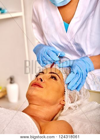 Woman middle-aged in spa salon with beautician. Beauty woman giving rejuvenating injections.