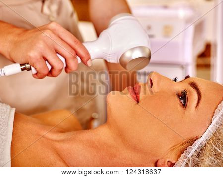 Close up of young woman in hat gets revitalizing electric ultrasonic facial massage at beauty salon.
