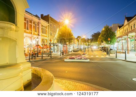 Wanganui, New Zealand - February 20, 2016: Wanganui, New Zealand - February 20, 2016: Night street scenes in city Wanganui historic and deco buildings around the light standard roundabout and light streaks of cars driving along Victoria Avenue through dow