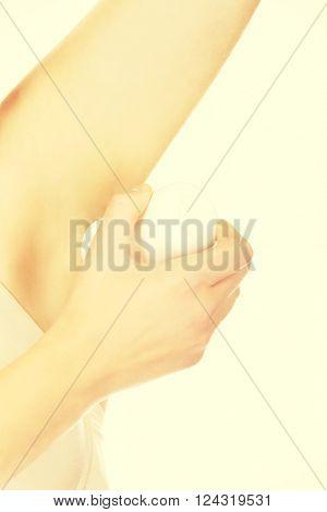 Beautiful young woman using antiperspirant