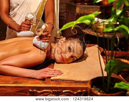 Woman having ayurvedic massage with pouch of rice. Cultural traditions of India.