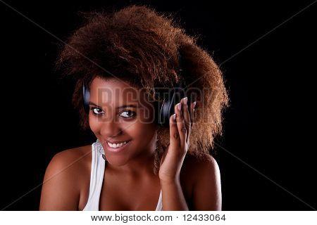 Beautiful Black Woman Happy Listening Music In Headphones, Isolated On Black Background. Studio Shot