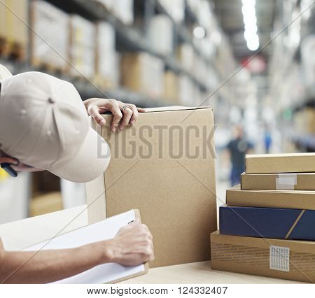 warehouse worker checking and recording goods received or to be shipped out.