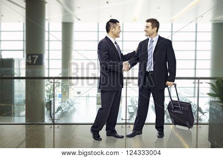 two businessmen one asian and one caucasian shaking hands and smiling at modern airport.