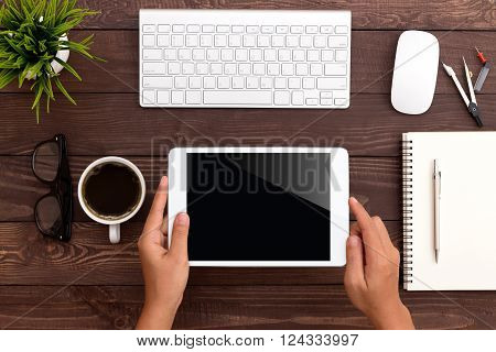 hand using white tablet on workspace top view