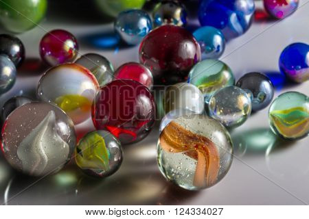Closeup view of translucent marbles on a shiny surface