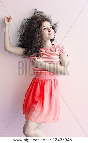 A young girl of Caucasian appearance dancing and dreams of a bright room on a summer day. Wavy curly hair and a red dress. Rest and be happy.