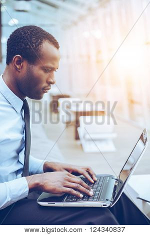 Concentrated at work. Side view of young and confident African man in formalwear working on laptop while sitting at his working place