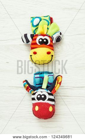 Two colorful wrist pals on the wooden background. Funny toys. Vibrant colors.