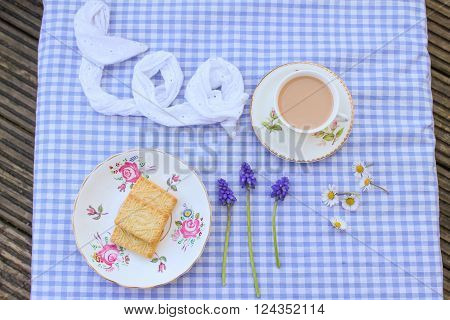 Milky tea and traditional unbranded custard cream biscuits with flowers on a gingham tablecloth