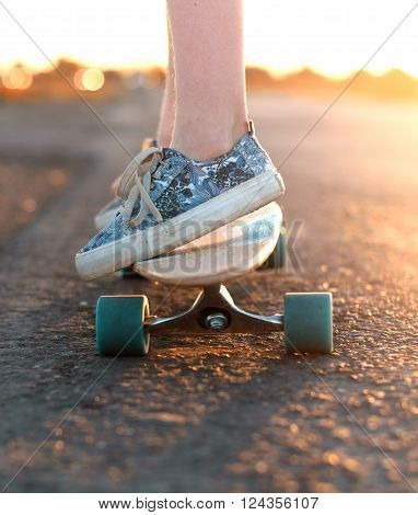 Teen rides a longboard on the road