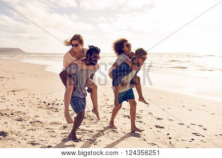 Two beautiful young couples walking along the beach with men giving piggyback ride to women. Piggyback games on beach vacation.