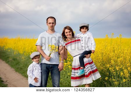 Family Of Four, Mother, Father And Two Boys, In A Oilseed Rape Field