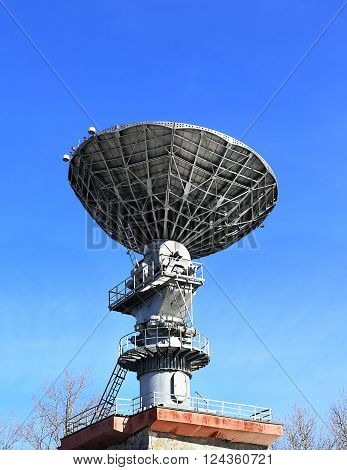 Dish antenna for the satellite communication with a metallic reflex reflector on the roof of the building
