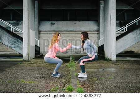 Two fitness women doing squat exercise workout outdoor on rainy winter day. Female athletes training and working out together.