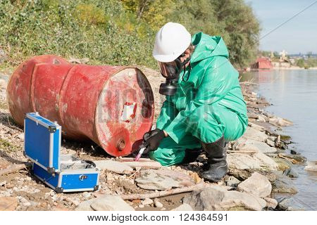Environmentalist taking sample at pollution site outdoors