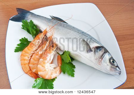 plate with sea bass prawns and parsley isolated on wooden background poster