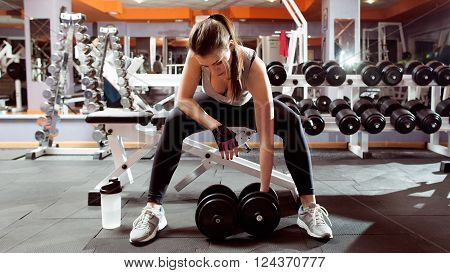 Professional athletic woman pumping up muscules with dumbbells in gym interior. Strong woman workout with dumbbell in gym, biceps exercise closeup. poster