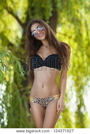 Beautiful sexy young girl with perfect slim figure with long wet hair and bathing suit in fashionable stylish sun glasses sunbathe, have fun at beach party. Focus on girl. ** Note: Soft Focus at 100%, best at smaller sizes