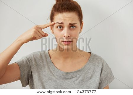 Closeup portrait indignant young freelancer woman looking at camera holding  finger at head with disgusting emotion on her face isolated grey wall background. Human emotion, reaction, expression.