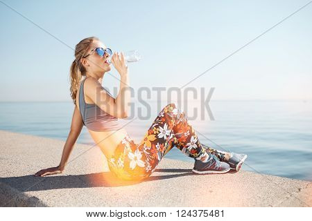 Muscular young female fitness blonde woman drinking water from bottle after running at beach. Woman sport runner resting taking a break with water bottle drink outside after training. Big size photo.