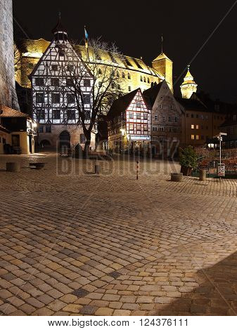 Nuremberg Germany - March 21 2016: The Castle seen from across the cobble stones of medieval square at the Durer house surrounded by old houses at night