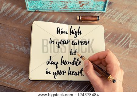 Retro effect and toned image of a woman hand writing on a notebook. Handwritten quote Aim high in your career but stay humble in your heart as inspirational concept image