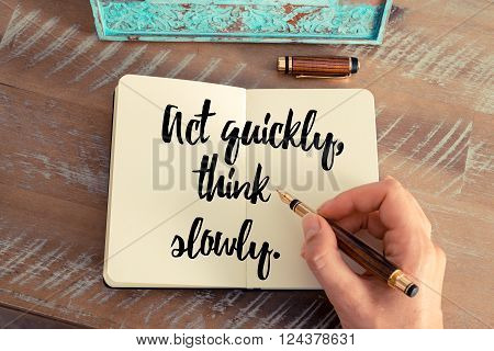 Retro effect and toned image of a woman hand writing on a notebook. Handwritten quote Act quickly think slowly as inspirational concept image