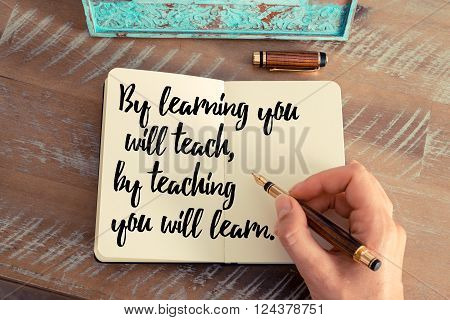 Retro effect and toned image of a woman hand writing on a notebook. Handwritten quote By learning you will teach, by teaching you will learn.  as inspirational concept image