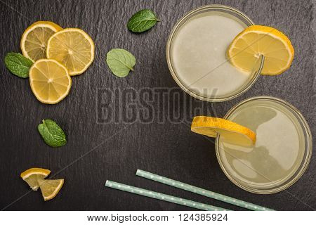 Glass of homemade lemonade with mint and lemon wedges on slate. Top view with copy space.