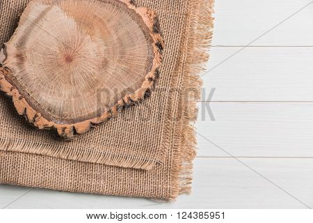 Wood plank board above burlap on wooden table, useful as a background. Top view with copy space.
