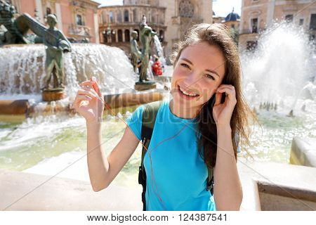 Happy smiling woman in Valencia is removing her earbuds. Spain. Travel and tourism concept.