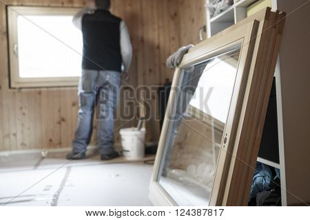 Worker in the background installing new three pane wooden windows in an old wooden house with a new window in the foreground. Home renovation sustainable living energy efficiency concept.