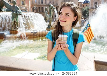 Tourist Girl drinking hot drink from disposable cup in Valencia Spain. Travel and tourism concept.