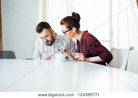 Two concentrated young businesspeople working together on the meeting in office