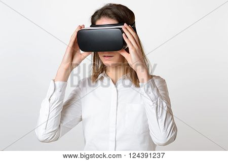 Single serious young woman in dark hair holding large 3D virtual reality viewing device over face on gray background