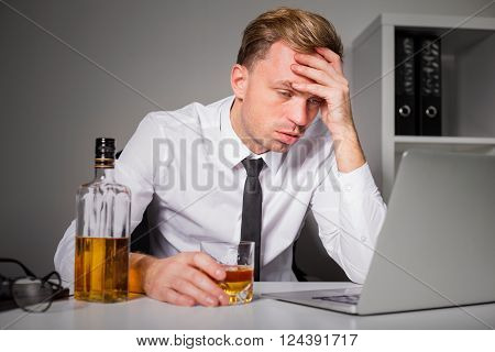 Tired man drinking at the office while working on laptop