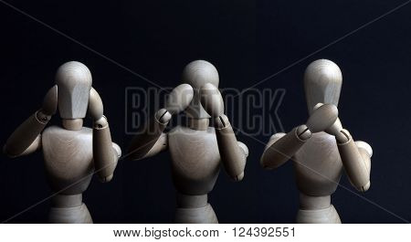 Hear see and be silent shown by a wooden mannequin 3 puppets next to each other