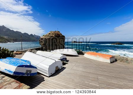 Summer seascape with fishermans boats on tropical island Tenerife, Canary in Spain. Playa de Roque de Las Bodegas with giant rock and high waves.