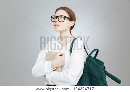 Thoughtful attractive girl student in glasses with backpack holding book and thinking