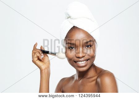 Happy afro american woman with makeup brush and towel isolated on a white background