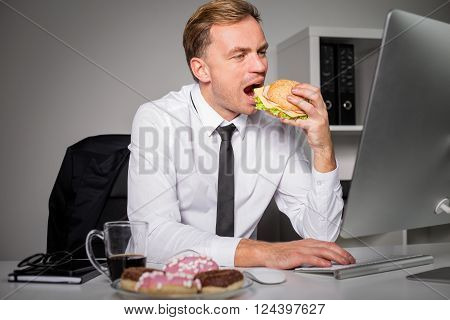 Busy man at the office eating fast food