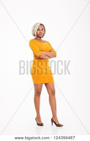 Full length of beautiful young african american woman in yellow dress standing with arms crossed over white background