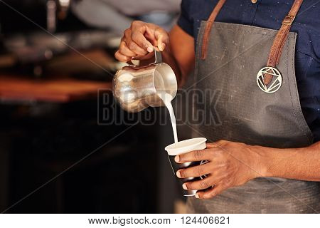Cropped image of an African barista carefully pouring milk from a stainless steel jug into a takeaway cup in a coffee shop poster